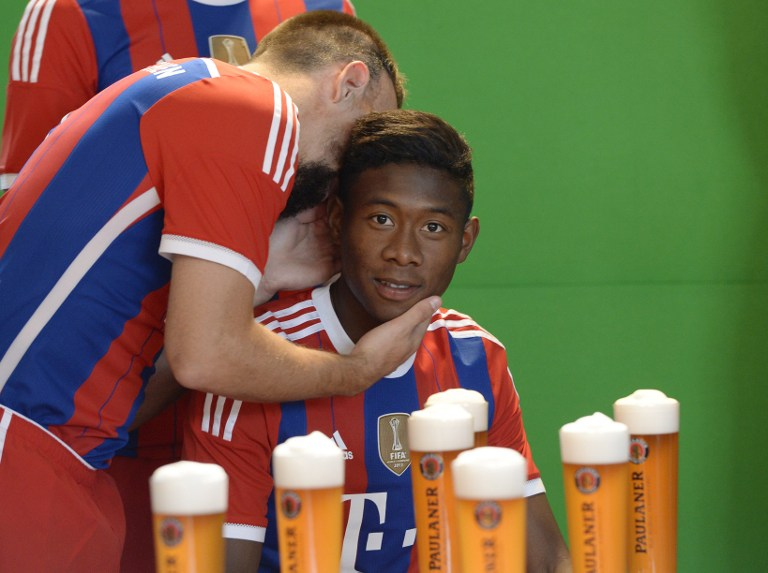 (L-R) Bayern Munich's French midfielder Franck Ribery and Bayern Munich's Austrian defender David Alaba speak at the set of a beer advertising photo shoot of German first division Bundesliga football club FC Bayern Munich in Munich, southern Germany, on August 31, 2014. AFP PHOTO/CHRISTOF STACHE